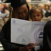 HADLEY GREEN/ Staff photo<br /> Danielle Osgood looks at the ceremony program while her son, Che'von Baker, 2, sits on her lap at the North Shore Community College commencement ceremony. 5/25/17