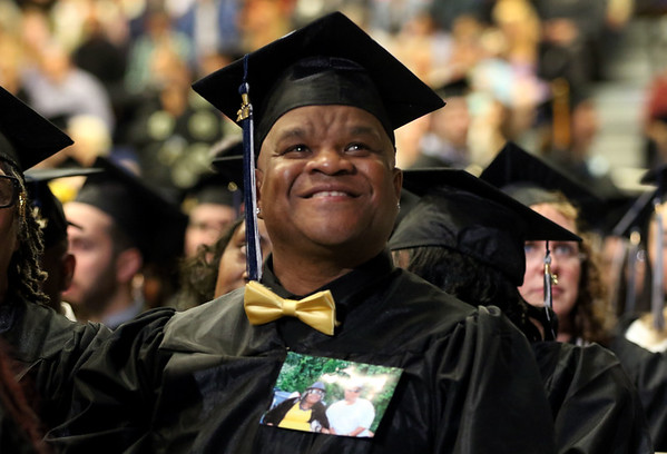 HADLEY GREEN/ Staff photo<br /> Gregory Wigfall smiles during the North Shore Community College commencement ceremony. He graduates in the Health and Human Services Division, and wears a photo of his mother, who passed away during his last semester, pinned to his graduation gown. 5/25/17