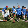 AMY SWEENEY/Staff photo. Christopher Harris, 7, from Riverside Elementary School, gets ready to kick the ball with the help of Tahg Coakley, a junior at Danvers High School. The school is hosted their Annual Special Olympics Danvers Day Games on Friday, May 19, at Danvers High School J. Ellison Morse Athletic Complex at Dr. Deering Stadium. The games are being held for all special needs children in the Danvers Public Schools grades K-12 and surrounding local communities.