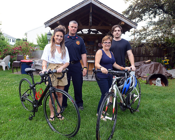 RYAN HUTTON/ Staff photo<br /> Donna Pimenta, second from right, stands with her husband Dan's training bicycle in their backyard in Peabody on Thursday afternoon along with her daughter Stephanie, left, her son Jake, right, and Peabody Fire Lt. Stephen Pellegrini, second from left. Dan Pimenta, a Peabody firefighter, was killed in a bicycle accident last year and had spent years riding for multiple sclerosis charities. This year during the Cape Cod Gateway ride, his team will be led by Pellegrini and joining the team will be Stephanie.