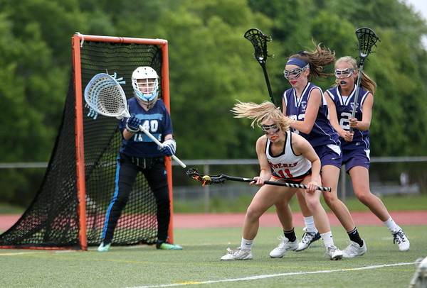 Staff photo/ HADLEY GREEN<br /> Beverly's Jill Trefry (11) looks for an opening to shoot while Peabody's Olivia Lavalle (40) guards the net at the Beverly v. Peabody girls lacrosse game.<br /> <br /> 05/28/2018