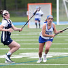 HADLEY GREEN/Staff photo<br /> Danvers' Isabel McKenna (15) runs with the ball while Hamilton-Wenham's Ele Hamilton (14) plays defense at the Danvers v. Hamilton-Wenham girls lacrosse game. <br /> <br /> 05/16/2018