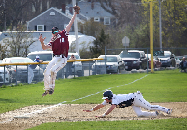 HADLEY GREEN/Staff photo<br /> Gloucester's Jack Sperry (19) jumps for the ball while Danvers' Zach Dillons (18) slides safely into third at the Gloucester v. Danvers baseball game at the Nate Ross Field in Gloucester.