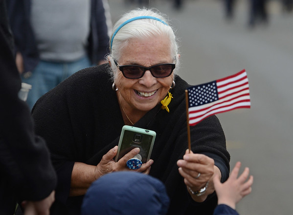MIKE SPRINGER/Staff photo<br /> Sheila Bell-Vaccaro gives a child a flag during the Memorial Day parade Monday in Danvers.<br /> 5/28/2018