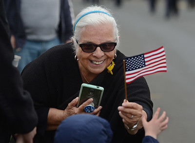 MIKE SPRINGER/Staff photo Sheila Bell-Vaccaro gives a child a flag during the Memorial Day parade Monday in Danvers. 5/28/2018