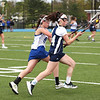 HADLEY GREEN/Staff photo<br /> Hamilton-Wenham's Ele Hamilton (14) runs with the ball while Danvers' Ashley Curcuru (9) defends her at the Danvers v. Hamilton-Wenham girls lacrosse game. <br /> <br /> 05/16/2018