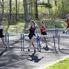 HADLEY GREEN/Staff photo<br /> Runners jump over hurdles at the Hamilton-Wenham, Ipswich and Masconomet track meet at Hamilton-Wenham High School.<br /> <br /> 05/09/2018
