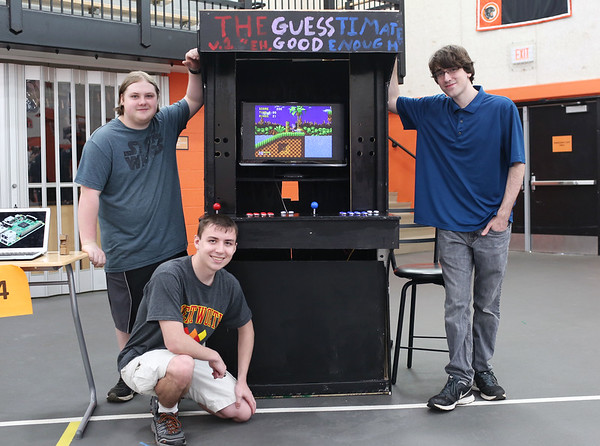 """Staff photo/ HADLEY GREEN<br /> From left, Josh Torrey, Trevor Schultz and Eric Argenio stand with an arcade machine that they built, the """"Guesstimate,"""" at the Beverly High School senior internship fair. <br /> <br /> 05/29/2018"""