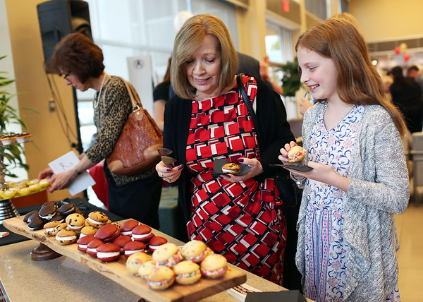 HADLEY GREEN/Staff photo<br /> Pat Jacobson and her granddaughter, Danielle Hargraves, of Boxford, taste cookies from Topsfield Bakeshop at the Gourmet Gala, a fundraiser for the North Shore Cancer Walk.<br /> <br /> 05/04/2018