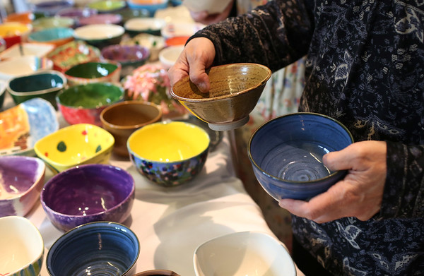 HADLEY GREEN/Staff photo<br /> Guests look at colorful bowls to choose from.