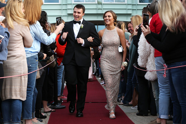 HADLEY GREEN/Staff photo<br /> Eric Faia and Annie Migliore walk down the red carpet before Marblehead High School's junior prom. <br /> <br /> 05/18/2018