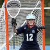 HADLEY GREEN/Staff photo<br /> Hamilton-Wenham goalie Callie Flanagan (12) shouts to her teammates while guarding the net at the Danvers v. Hamilton-Wenham girls lacrosse game. <br /> <br /> 05/16/2018