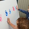 RYAN HUTTON/ Staff photo<br /> Scarlet Theriault, 3, left, and Cuillin Swan-Grimes, 4, right, add their hand prints to the Raise Up Your Hands! wall at the Salem Farmer's Market on Thursday. The wall is meant to draw attention to the plight of migrant children being separated from their parents at the US-Mexican border.