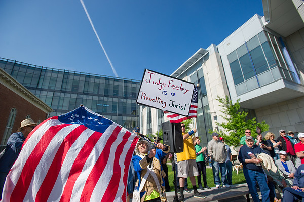 AMANDA SABGA/Staff photo<br /> <br /> Boris Koski, of Belchertown holds up a sign and flag during a rally outside of Salem Superior Court pushing for the impeachment of Judge Timothy Feeley.<br /> <br /> 5/24/18