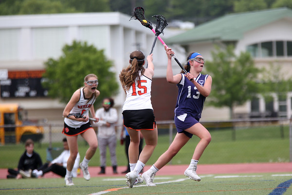 Staff photo/ HADLEY GREEN<br /> Peabody's Amber Kiricoples (13) shoots and scores while Beverly's T Crowell (15) plays defense at the Beverly v. Peabody girls lacrosse game.<br /> <br /> 05/28/2018