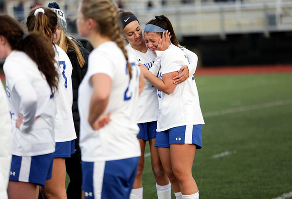 HADLEY GREEN/ Staff photo<br /> Danvers' Rebecca Rocker (5) comforts captain Madison Pesce (15) after the Falcons lose to Winchester in the Division 2 North championship game at the Manning Field in Lynn.<br /> <br /> 11/12/2018
