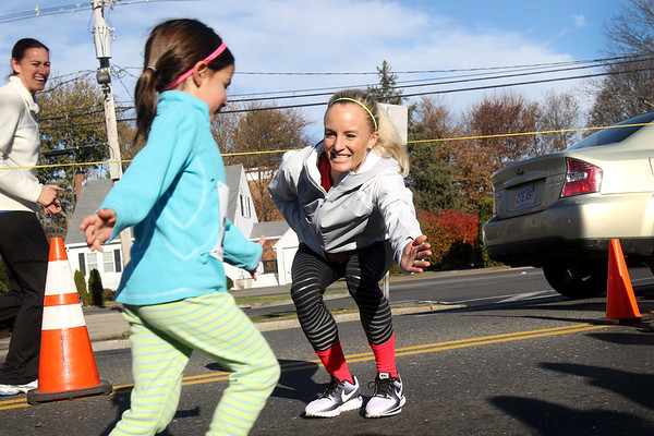 HADLEY GREEN/Staff photo<br /> Marblehead native and recent New York City Marathon women's champion Shalane Flanagan high-fived young runners at the Kid's Fun Run before the annual Back the Track 5K in Marblehead. <br /> <br /> 11/25/17