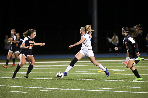 HADLEY GREEN/Staff photo<br /> Danvers' Sarah Unczur (16) runs down the field while Beverly's Alyssa Moreland (11) plays defense at the Danvers v. Beverly Division 2 North quarterfinal girls soccer game at Danvers High School.<br /> <br /> 11/04/17