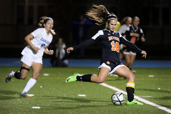 HADLEY GREEN/Staff photo<br /> Beverly's Stephanie MacLeod (18) kicks the ball down the field while Danvers' Hannah Lejeune (8) plays defense at the Danvers v. Beverly Division 2 North quarterfinal girls soccer game at Danvers High School.<br /> <br /> 11/04/17