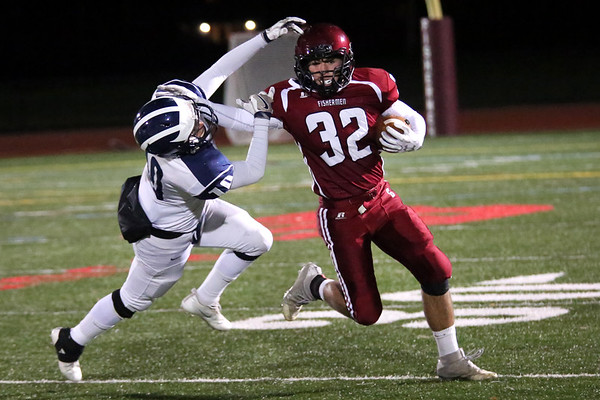 HADLEY GREEN/Staff photo<br /> Gloucester's Marc Smith (32) fends off Swampscott defender Ethan Friedman (10) at the Gloucester v. Swampscott football game at Gloucester High School.<br /> 11/10/17