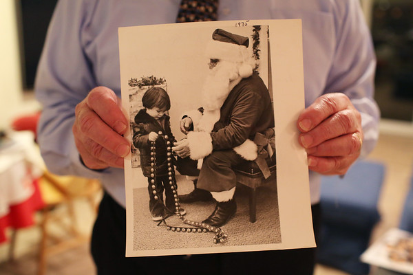 HADLEY GREEN/Staff photo<br /> Charlie Bucci Jr. holds a photo of his father, Charlie Bucci Sr., dressed up as Santa Claus. <br />  <br /> 11/16/17
