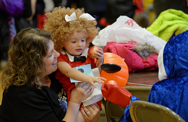 RYAN HUTTON/ Staff photo<br /> Dressed as the Little Orphan Annie, Aiyana Couto, 2, hands an apple to her friend Aiden Tirell, 7, dressed as a boxer, with the help of her grandmother Paula Couto at the Peabody Halloween celebration at the Knights of Columbus hall on Thursday.