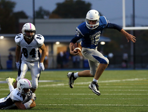 DAVID LE/Staff photo. Danvers senior quarterback Dean Borders leaps out of a tackle from diving Peabody senior Pat Maguire (23). 10/21/16