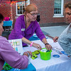 PARKER FISH/ Photo. Sandra Griffel of Beverly helps guests at the Beverly Arts District table during the Beverly Block Party on Saturday. 9/17/16