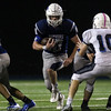 DAVID LE/Staff photo. Danvers senior captain Matt Andreas (10) bursts through a hole in the offensive line and heads downfield. 10/21/16