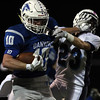DAVID LE/Staff photo. Danvers senior captain Matt Andreas (10) stiff arms senior Pat Maguire (23) during a first half run. 10/21/16