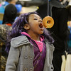 "RYAN HUTTON/ Staff photo<br /> Dressed as the character Mal from the Disney Channel show ""Descendants"", Tiffany Nvuta, 7, competes in the donut-on-a-string eating contest at the Peabody Halloween celebration at the Knights of Columbus hall on Thursday."