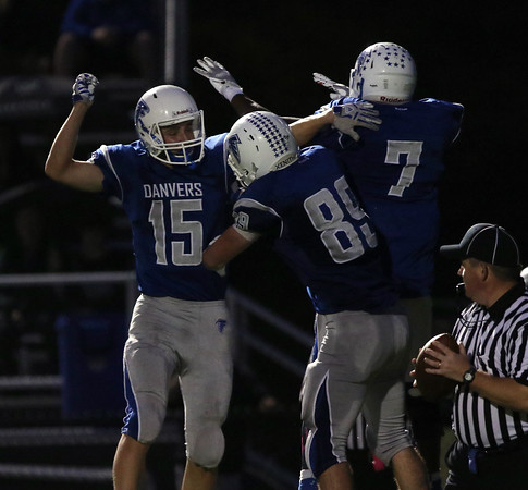 DAVID LE/Staff photo. Danvers senior Zach Turner (15) Kieren Moriarty (89) and Tahg Coakley (7) celebrate Coakley's touchdown during the first half against Peabody. 10/21/16