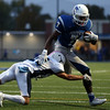 DAVID LE/Staff photo. Danvers senior Tahg Coakley (7) manages to run through a diving tackle from Peabody senior Cedric Gutierrez (21). 10/21/16