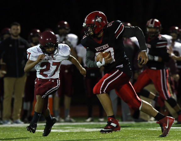DAVID LE/Staff photo. Salem tight end Jayco Pena (87) sprints upfield while Gloucester's Nicholas Filho (27) closes in for a tackle. 10/14/16.