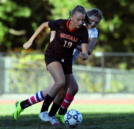 DAVID LE/Staff photo. Beverly senior Tessa Armbroster (19) turns upfield while being defended by Swampscott senior Bridget Cullinane. 10/6/16.