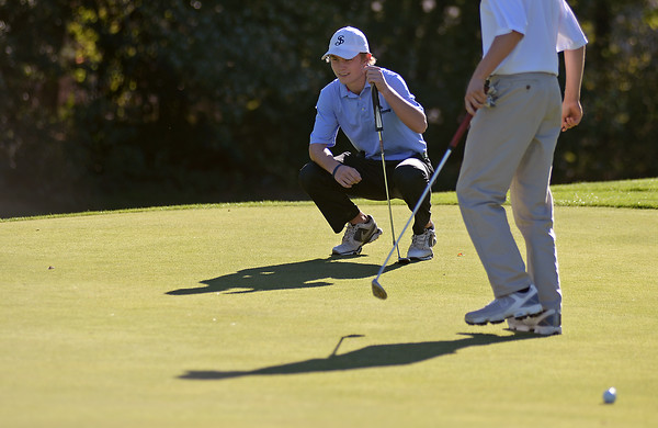 RYAN HUTTON/ Staff photo<br /> St. John's Prep's Griffin Chenard, 18, lines up his putt on the 13th hole's green as teammate Drew Semons, 15, retrieves his ball from the hole during practice at the Middleton Golf Course on Wednesday.