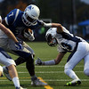 DAVID LE/Staff photo. Peabody senior Pat Maguire (23) drags down Danvers senior Tahg Coakley (7) as teammate Marcus Barker (10) also closes in. 10/21/16