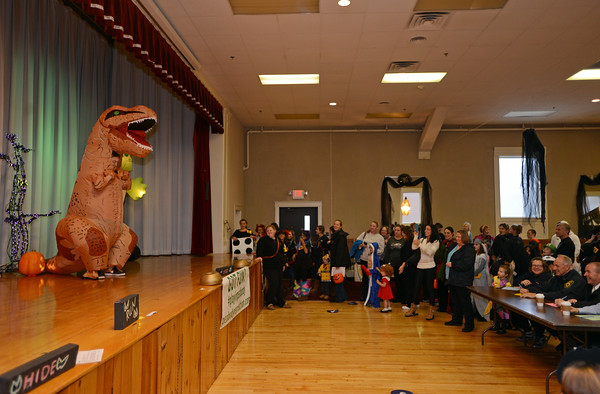 RYAN HUTTON/ Staff photo<br /> Domenic Gaeta, 12, takes the stage dressed as a T-Rex during the costume contest at the Peabody Halloween celebration at the Knights of Columbus hall on Thursday.