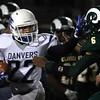 DAVID LE/Staff photo. Danvers senior Justin Curtis (22) stiff arms Lynn Classical junior Ishmael Johnson (6) along the sideline. 9/30/16.