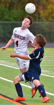 Miles  Brengle of Ipswich, manages to head the ball away from Hamilton Wenham's Eli Leonard during the game at Ipswich High School<br /> <br /> Photo by JoeBrownPhotos.com