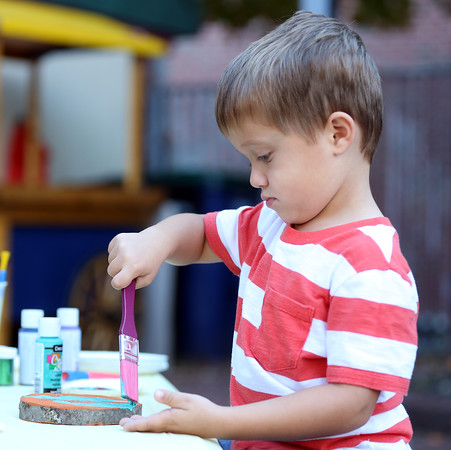 DAVID LE/Staff photo. Three-year-old Joe Coletti, of Salem, paints a round orange pumpkin at Mayor's Night Out on Artist's Row on Friday afternoon. 10/7/16.