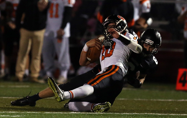 DAVID LE/Staff photo. Marblehead senior Jack Knight (6) drags down Beverly's Nick Berry (10). 10/7/16.