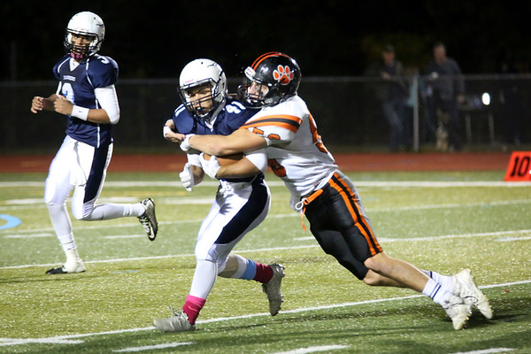 HADLEY GREEN/Staff photo<br /> Beverly's Hans Holm (56) tackles Peabody's Angel Paulino (41) at the Peabody v. Beverly football game at Peabody High School.<br /> <br />  10/20/17