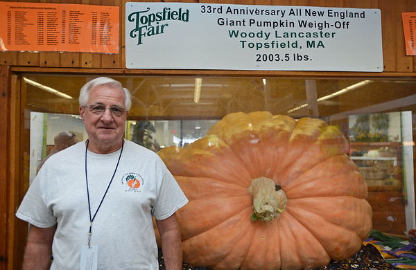 RYAN HUTTON/ Staff photo<br /> Topsfield's Woody Lancaster stands next to his award-winning  2,003.5 pound pumpkin in it's place of honor at the vegetable barn at the Topsfield Fair on Monday.