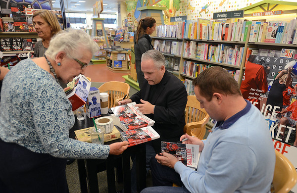 "RYAN HUTTON/ Staff photo<br /> Authors Casey Sherman, center, and Dave Wedge, right, sign copies of their book ""Ice Bucket Challenge: Pete Frates and the Fight Against ALS"" for Beverly native Annette Divicenzo, left, at the Barnes and Nobel in Peabody on Sunday afternoon. Divincenzo is the grandmother of Tommy Haugh, a long-time friend of Pete Frates."