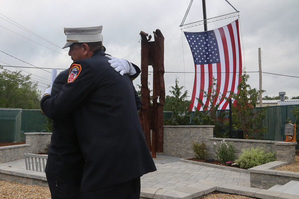 Photo/Reba Saldanha Salem Fire Department deputy Gerry Giunta and NYFD retired chief of special operations Fred LaFemina embrace during the dedication of a 9/11 memorial at Beverly Municipal Airport Sunday Sept 11, 2016.