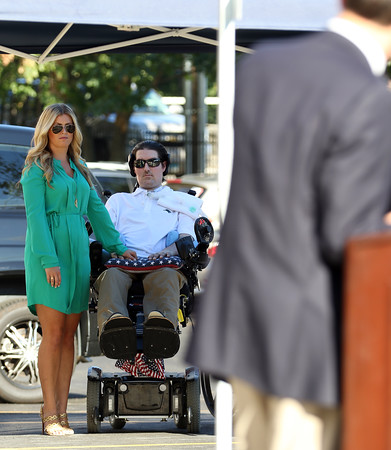 DAVID LE/Staff photo. Pete and Julie Frates, hold hands and listen to Beverly Mayor Mike Cahill during a dedication ceremony for Peter Frates Hall on the campus of Endicott College in Beverly. 9/13/16.