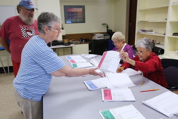 KEN YUSZKUS/Staff photo.  Voter Catherine Green receives ballots from Aspacia Cassidy for herself and her husband Michael Franceschi to vote at the Ward 5 Precinct 1 polling place at the Kiley Brothers Memorial School in Peabody.  Dorothy Melanson is sitting at the table in the background.    09/08/16