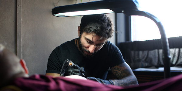 DAVID LE/Staff photo. Matt Murray, and his identical twin brother Ryan, own and run Black Veil Tattoo Studio on Cabot Street in Beverly. The brothers were recently featured on Spike TV's Ink Master show. Matt starts work on a tattoo for Monserrat College of Art sophomore Alexis Ferris on Friday afternoon. 9/2/16.
