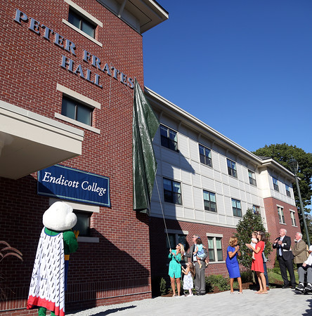 DAVID LE/Staff photo. Julie Frates unveils the Peter Frates Hall sign on the brand new residence hall at Endicott College. 9/13/16.
